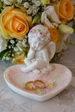 Två guld- vigselringar ligger på ett uppläggningsfat i en rosform med ängelskulpturen nära bride&en x27; s-bukett Arkivfoto