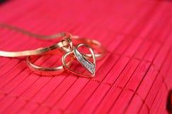 Två guld- vigselringar och guld- hjärta Royaltyfria Foton