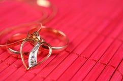 Två guld- vigselringar och guld- hjärta Royaltyfri Foto