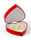 Två guld- vigselringar som ligger i en röd hjärta-formad ask Arkivbilder