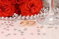 Två guldbröllopcirklar med röda rosor Arkivfoto