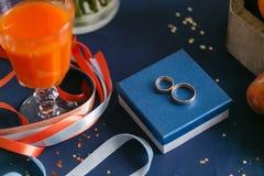 Två guldbröllopcirklar som lägger på blåttyttersida tillbehör för bruden och brudgummen Förberedelse för ceremonin royaltyfria bilder