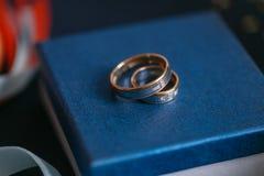 Två guldbröllopcirklar som lägger på blåttyttersida tillbehör för bruden och brudgummen Förberedelse för ceremonin royaltyfri fotografi