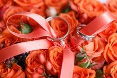 Två guldbröllopcirklar som lägger på magasinet av orange rosor tillbehör för bruden och brudgummen Förberedelse för royaltyfri fotografi