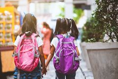 Två gulliga asiatiska barnflickor med handen för innehav för skolapåse och att gå tillsammans i skolan arkivbild