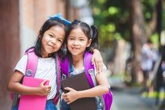 Två gulliga asiatiska barnflickor med skolapåsen som tillsammans rymmer en bok i skolan royaltyfri foto
