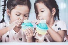 Två gulliga asiatiska barnflickor som har gyckel som äter den blåa muffin Arkivbild