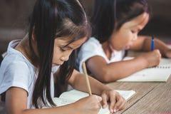 Två gulliga asiatiska barnflickor som läser en bok och skriver en anteckningsbok i klassrumet fotografering för bildbyråer
