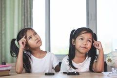 Två gulliga asiatiska barnflickor som tänker, när göra läxa i rummet royaltyfria bilder