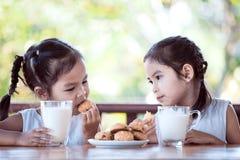 Två gulliga asiatiska flickor för litet barn äter kakor med mjölkar royaltyfri foto