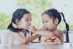 Två gulliga asiatiska flickor för litet barn äter kakor med mjölkar fotografering för bildbyråer