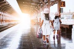 Två gulliga asiatiska små flickor som rymmer resväskan och att gå Royaltyfri Foto