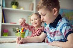 Två gulliga barn som drar med färgrika blyertspennor Arkivbilder