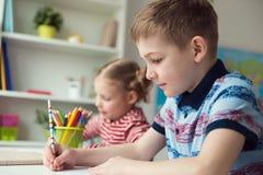 Två gulliga barn som drar med färgrika blyertspennor Royaltyfri Bild
