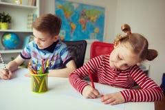 Två gulliga barn som drar med färgrika blyertspennor Arkivfoton