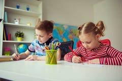 Två gulliga barn som drar med färgrika blyertspennor Royaltyfri Foto