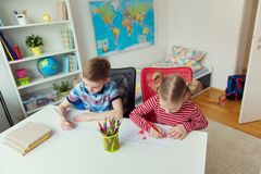 Två gulliga barn som drar med färgrika blyertspennor Royaltyfri Fotografi