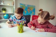 Två gulliga barn som drar med färgrika blyertspennor Arkivfoto