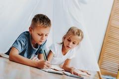 Två gulliga barn som tillsammans hemma studerar royaltyfri fotografi