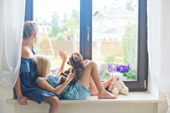 Två gulliga europeiska litet barnflickor som sitter på fönsterbräda nära fönster Royaltyfri Fotografi
