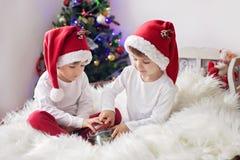 Två gulliga förtjusande pojkar som tycker om godisar på jultid Arkivfoton