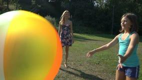 Två gulliga flickor av olika åldrar deras moderlek med en uppblåsbar boll för stor färgrik regnbåge stock video