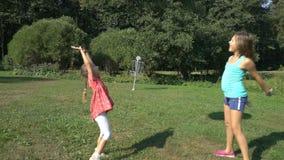 Två gulliga flickor av olika åldrar spelar med en uppblåsbar boll för stor färgrik regnbåge arkivfilmer