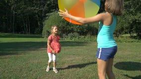 Två gulliga flickor av olika åldrar spelar med en uppblåsbar boll för stor färgrik regnbåge stock video