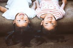 Två gulliga flickor för litet barn ligger på deras baksidor på soffan arkivfoto