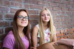 Två gulliga flickor som framme sitter av en tegelstenvägg Arkivbild