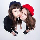 Två gulliga flickor som har gyckel och gör roliga framsidor Arkivbild