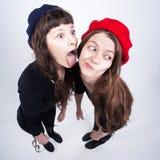 Två gulliga flickor som har gyckel och gör roliga framsidor Royaltyfria Bilder