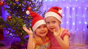 Två gulliga flickor som ler och vinkar på kameran i en jultomtenhatt I bakgrunden, ljusen och girlanderna av julgran stock video