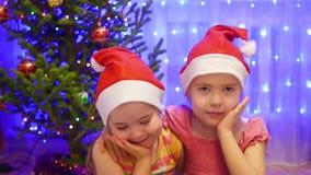 Två gulliga flickor som ler och vinkar på kameran i en jultomtenhatt I bakgrunden, ljusen och girlanderna av julgran