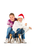 Två gulliga flickor som rider på en pulka Royaltyfria Bilder