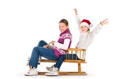 Två gulliga flickor som rider på en pulka Royaltyfri Fotografi