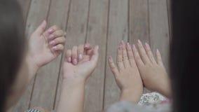 Två gulliga flickor som sitter utomhus tillsammans att prata om ny manikyr och att visa fingrar och, spikar Flickvänsamtal arkivfilmer