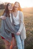 Två gulliga flickor utomhus på solnedgången Arkivfoto