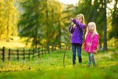 Två gulliga gulliga små flickor som har gyckel under skogvandring på härlig höstdag i italienska fjällängar Arkivbilder