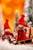 Två gulliga lilla röda juldockor med en släde arkivfoto