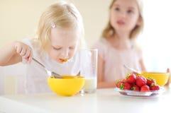 Två gulliga lilla systrar som äter sädesslag i ett kök Arkivfoto