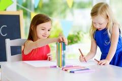Två gulliga lilla systrar som drar med färgrika blyertspennor på en daycare Idérika ungar som tillsammans målar Arkivbild