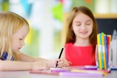Två gulliga lilla systrar som drar med färgrika blyertspennor på en daycare Idérika ungar som tillsammans målar Fotografering för Bildbyråer