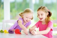 Två gulliga lilla systrar som har gyckel samman med färgrik modellera lera på en daycare arkivfoto