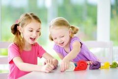 Två gulliga lilla systrar som har gyckel samman med färgrik modellera lera på en daycare royaltyfria bilder