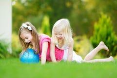 Två gulliga lilla systrar som har gyckel tillsammans på gräset Royaltyfri Foto