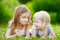 Två gulliga lilla systrar som lägger i gräset Royaltyfria Bilder