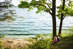 Två gulliga lilla systrar som sitter av sjön som tycker om härlig solnedgångsikt Barn som undersöker naturen royaltyfri bild