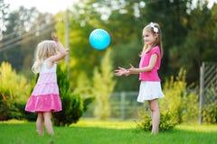 Två gulliga lilla systrar som spelar bollen tillsammans på gräset Arkivbild