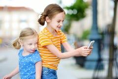 Två gulliga lilla systrar som spelar den utomhus- mobilleken på deras smarta telefoner Fotografering för Bildbyråer